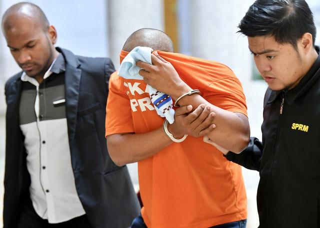 Suspek diiringi pegawai SPRM di mahkamah hari ini - Gambar Bernama