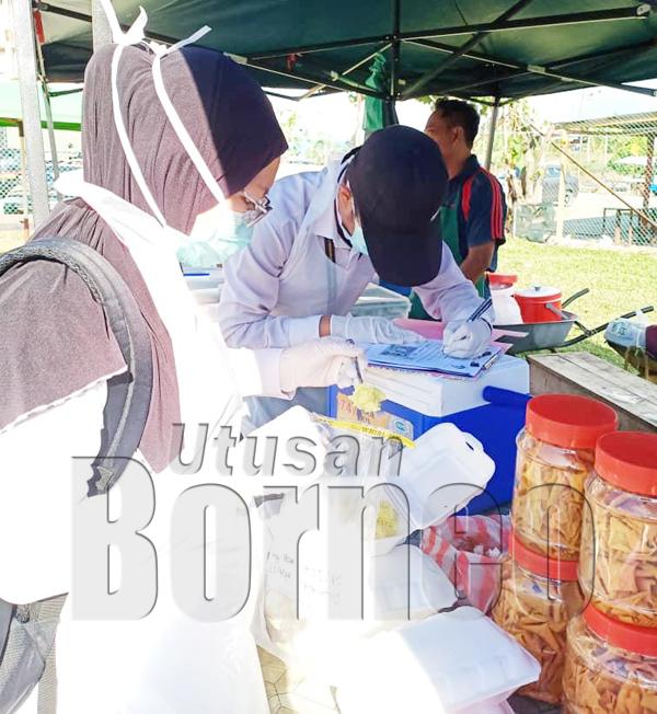 PENOLONG pegawai persekitaran mengambil sampel makanan untuk dianalisa.