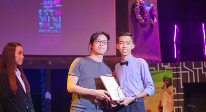 Muhammad Alif (kanan) menerima trofi Anugerah  Filem Terbaik (kategori sekolah)  daripada seorang pembikin filem Sarawak, Nova Goh yang juga juri untuk MFF ke-15.