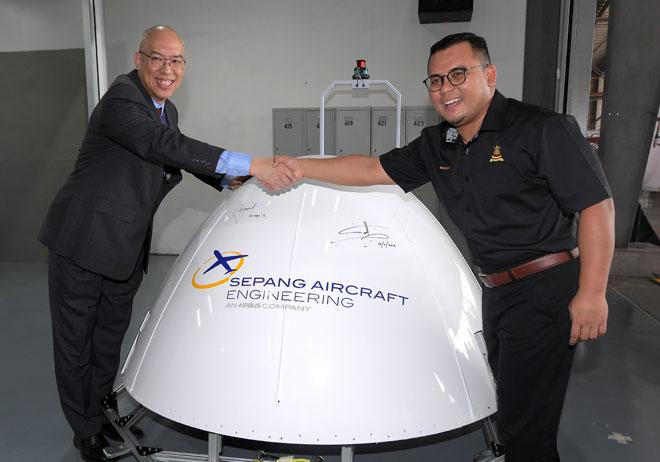 Amirudin (kanan) bersalaman dengan Raymond pada majlis perasmian Workshop Smart Radome di Sepang Aircraft Engineering semalam. — Gambar Bernama