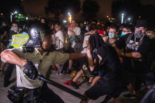 Anggota polis menghayunkan cota ke arah penunjuk perasaan yang menyertai perhimpunan di luar Dewan Perwakilan bagi membantah usul rang undang-undang ekstradisi di Hong Kong pada awal pagi semalam. — Gambar AFP