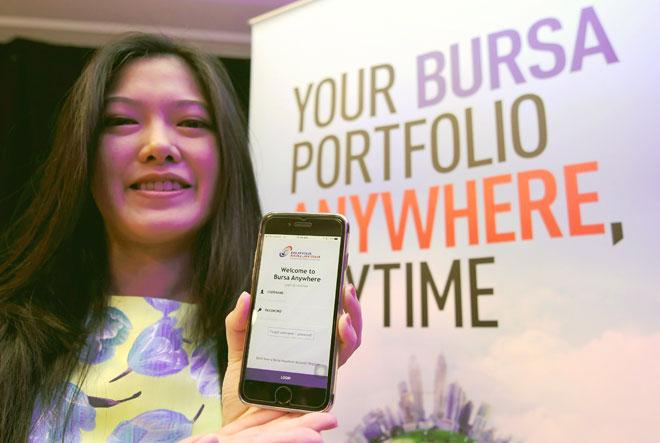 Ketua Pengembangan dan Pemasaran Perniagaan Utama UOB Kay Hian, Jean Soo menunjukkan aplikasi Bursa Malaysia 'Anywhere' yang baharu dilancarkan semalam. — Gambar Bernama