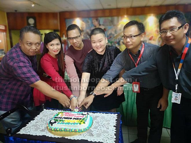 Saiful (tiga kiri), Lau (tiga kanan) serta tetamu lain menyempurnakan upacara memotong kek.