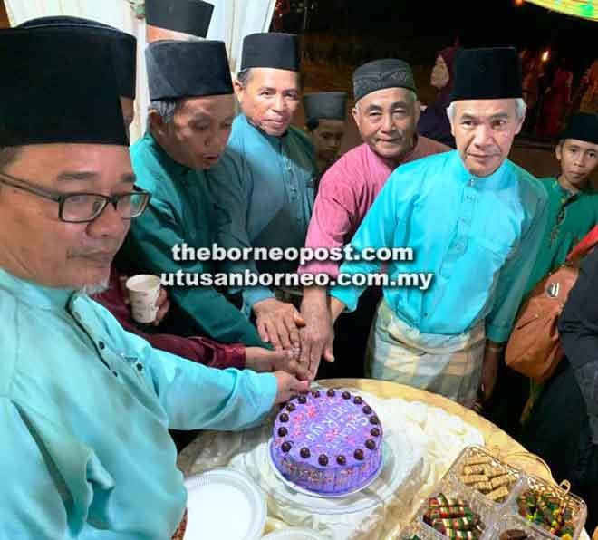 Harbi (kanan) dan Sameon(kiri) bersama tetamu lain yang mengunjungi khemahnya memotong kek sambutan raya.