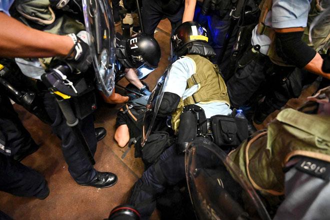 Polis menangkap penunjuk perasaan semasa pertelingkahan di daerah Mong Kok                        di Kowloon selepas satu perarakan ke terminal kereta api di Kowloon Barat untuk membantah                    rang undang-undang ekstradisi di Hong Kong kelmarin. — Gambar AFP