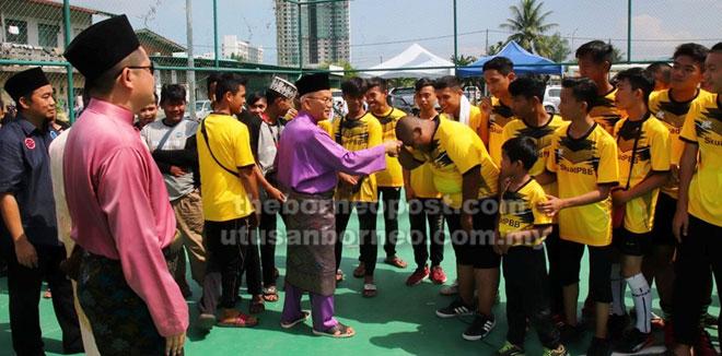 Talib semasa merasmikan Pertandingan Futsal Tertutup Skuad PBB Junior bersalaman dengan kanak-kanak dan remaja yang menyertai pertandingan futsal tersebut.