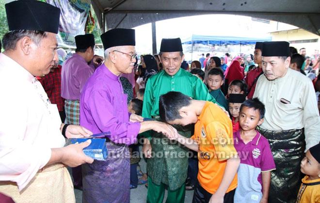 Talib menyampaikan duit raya kepada kanak-kanak di Majlis Belanggar Qapong Sebezaw.