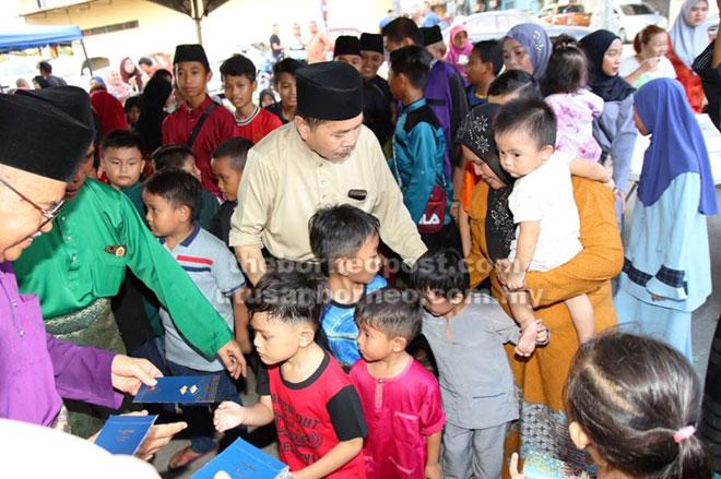 Talib (kiri) menyampaikan duit raya sebagai sedekah jariah kepada kanak-kanak.