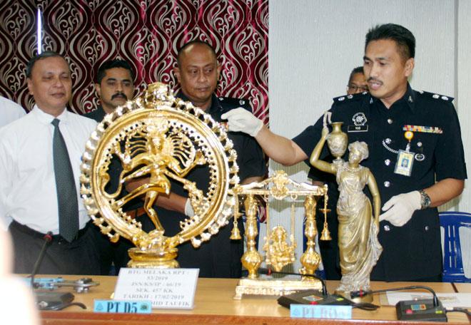 Yusharifuddin (kanan) menunjukkan patung bersadur emas yang dirampas pihak polis hasil tangkapan suspek berkumpulan pada sidang media di Ibu Pejabat Polis Kontinjen (IPK) Melaka di Ayer Keroh, Melaka, semalam. — Gambar Bernama