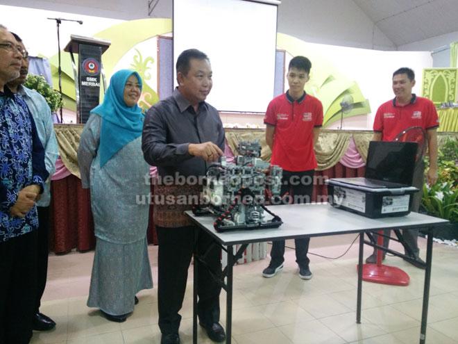 Dr Azhar melakukan gimik perasmian Majlis                           Penutupan Karnival Bahasa Inggeris dan Robotik Peringkat                        Negeri Sarawak di SMK Merbau malam kelmarin sambil                                      disaksikan Shirini (kiri) serta yang lain.