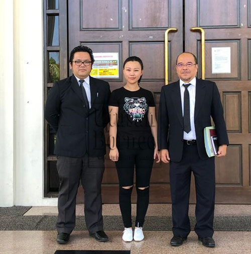 Yuan Xi bersama peguamnya semasa berada di Kompleks Mahkamah Kuching.