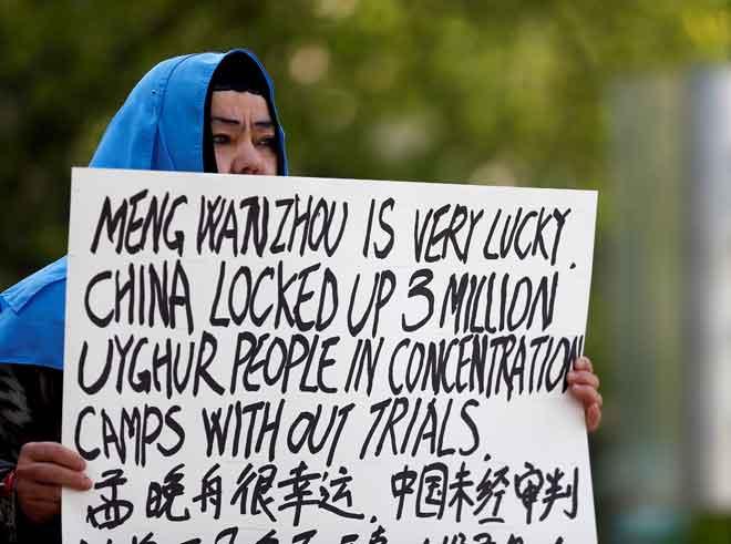 Dilibair Yusuf memegang poster yang menyelar layanan China ke atas etnik Uighur di wilayah Xinjiang semasa kemunculan Ketua Kewangan Huawei Meng Wanzhou di Mahkamah Agung British Columbia di Vancouver, Kanada pada 8 Mei. — Gambar Reuters