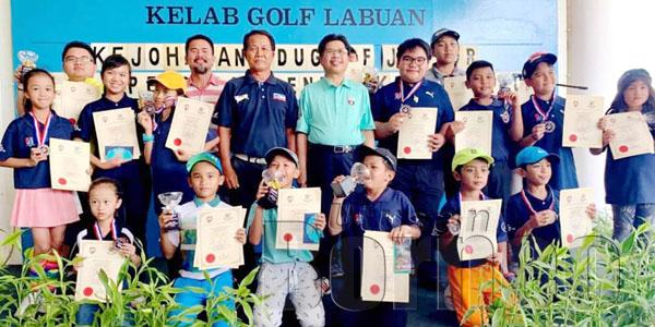 RAISIN (berdiri enam dari kanan) bersama Donnie, Jius dan pemain Pelapis Sabah semasa majlis penyampian hadiah Kejohanan Kejohanan Golf Junior Piala Pengarah Pendidikan Wilayah Persekutuan Labuan 2019 di LGC, Rabu lalu.