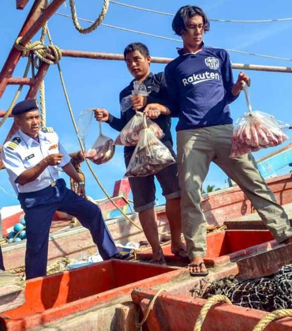 Ismail (kiri) menunjukkan hasil tangkapan ikan yang dilakukan secara haram oleh nelayan warga asing selepas dua bot nelayan asing yang berjaya ditahan bersama 21 awak-awak dari negara Vietnam di pekarangan pejabat APMM Tok Bali,                 Pasir Putih semalam. — Gambar Bernama