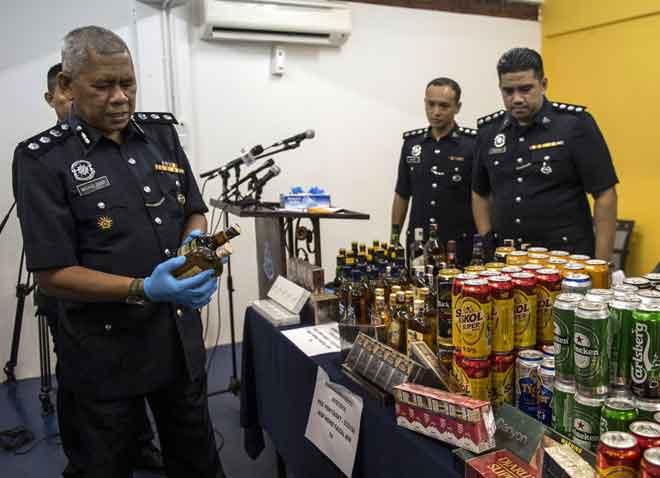 Mohd Zani (kiri) memeriksa barangan yang dirampas pada sidang media                    di Balai Polis Damansara, Petaling Jaya semalam. — Gambar Bernama