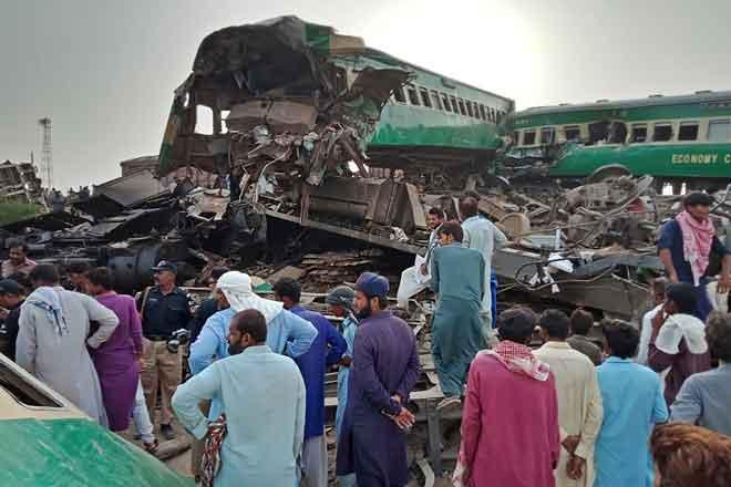 Penduduk setempat berhimpun sekitar bangkai gerabak di tapak di mana dua kereta api berlanggar di daerah                         Rahim Yar Khan di wilayah Punjab, Pakistan kelmarin. — Gambar AFP