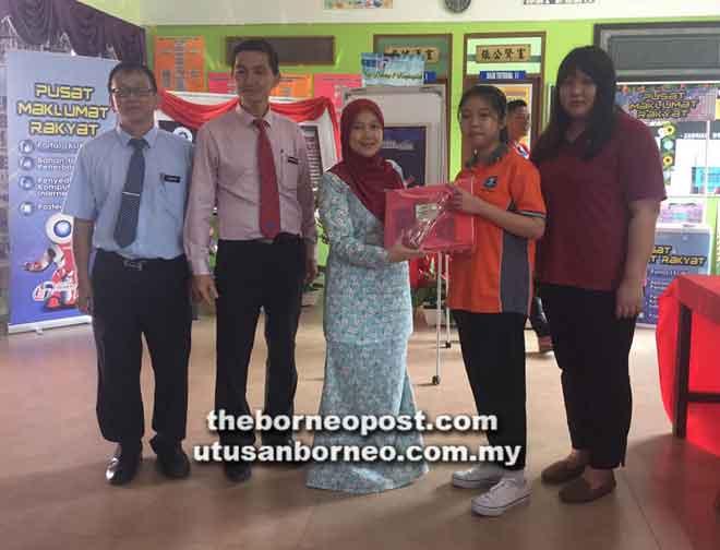 Norliza (tiga kiri) menyampaikan hadiah kepada salah seorang pelajar pada pertandingan kaligrafi pada Program Pengimarahan PMR Jabatan Penerangan Malaysia Daerah Sarikei di SMK Tinggi Sarikei, semalam.