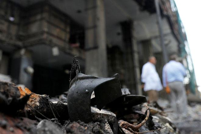 Barang milik mangsa dilihat di celah runtuhan batu di hadapan muka bangunan Institut Kanser Negara yang rosak selepas kebakaran semalaman susulan letupan kuat di Kaherah, Mesir kelmarin. — Gambar Reuters
