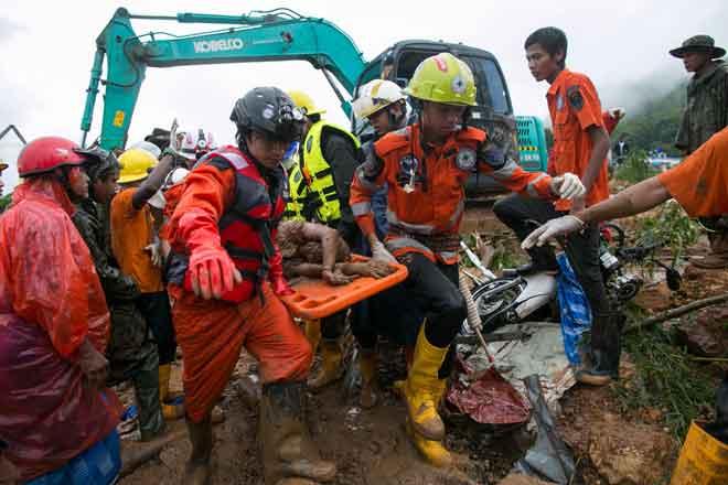 Pasukan penyelamat membawa mayat mangsa tanah runtuh di pekan Paung semalam. — Gambar AFP