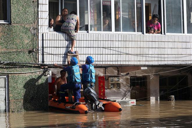 Pekerja penyelamat membantu penduduk yang terkandas dalam banjir selepas Taufan Lekima melanda bandar Linhai di Taizhou, wilayah Zhejiang, China kelmarin.  — Gambar Reuters
