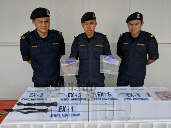 Boon (tengah) menunjukkan rampasan syabu semasa penahanan suspek, turut kelihatan panah ikan yang turut ditemukan di dalam bot pam dinaiki suspek.