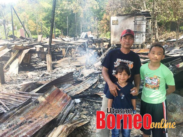 James (kiri) bersama dua anaknya hanya mampu melihat rumah mereka yang terbakar