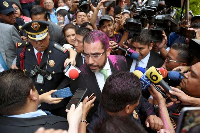 Orta Martinez dengan rambut disembur merah jambu oleh seorang penunjuk perasaan, dikerumuni wartawan ketika cuba menenangkan protes mengecam polis di hadapan Kementerian Keselamatan Awam di Kota Mexico, kelmarin. — Gambar AFP