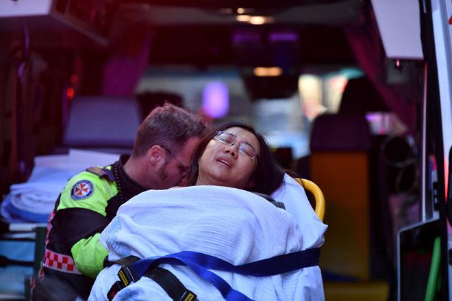 Seorang wanita yang dipercayai ditikam dari belakang diusung ke dalam ambulans ketika polis menyiasat tempat kejadian di Sydney, semalam. — Gambar Reuters