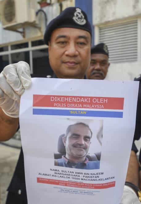 DSP Wan Fauzi menunjukkan fotofit suspek berusia 50-an yang diburu polis kerana terlibat dalam kes tetak bekas isterinya menggunakan sebilah golok di hadapan sebuah bank, di Kuala Krai pada 1 Ogos lalu pada sidang media di Ibu Pejabat Polis Daerah Kuala Krai, Kuala Krai semalam. — Gambar Bernama