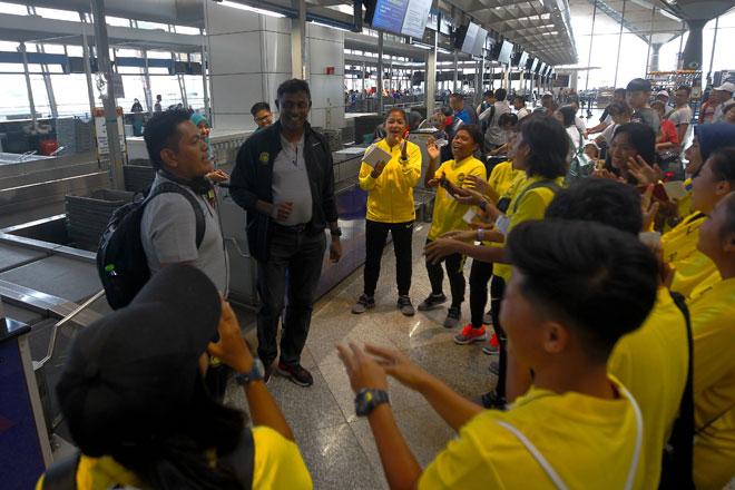 Jacob (dua kiri) bersorak bersama para pemain sebelum berlepas ke Bangkok untuk menghadapi Kejuaraan Wanita AFF 2019 di Lapangan Terbang Antarabangsa Kuala Lumpur semalam. — Gambar AFP