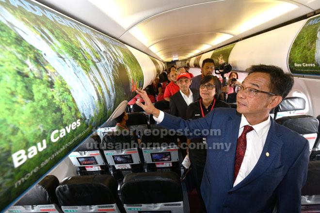 Abdul Karim bersama Sharzede (dua kanan) dan Abdul Aziz (tiga kanan) serta yang lain memerhatikan paparan destinasi menarik di Sarawak yang dipaparkan dalam iklan pada ruang simpanan bagasi dalam pesawat AirAsia yang dilancarkan, semalam.