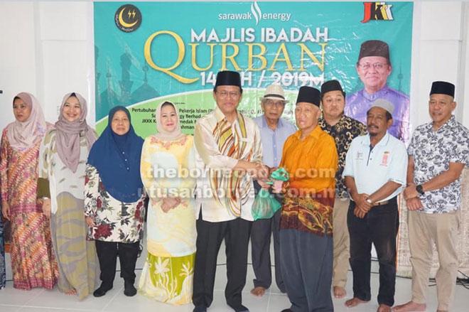 Dr Abdul Rahman mengagihkan daging korban di Surau-Ar Rahman Kampung Temedak Melayu di Kuching kelmarin.
