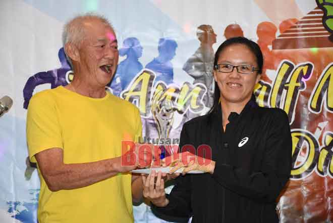 Kuo (kiri) menyampaikan hadiah kepada Siaw yang muncul juara bagi kategori wanita terbuka 21KM.