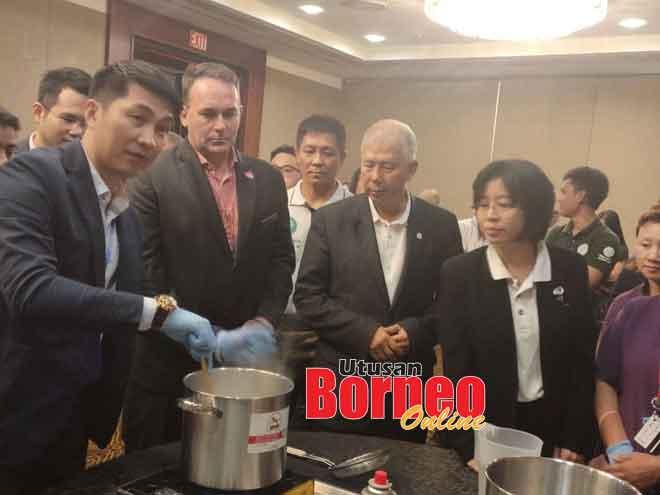 (dari dua kiri) Watts, Ting dan Chong bersama yang lain melihat pegawai Ecolab Azymie Yusof membuat demontrasi menghasilkan sabun baharu daripada sabun terpakai dari Hilton Kuching.