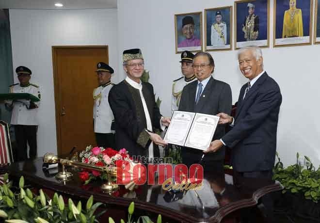Junaidi (kiri) menerima dokumen serah tugas daripada Abang Wahap sebagai Datuk Bandar DBKU yang baharu disaksikan Abang Johari (tengah).  — Gambar Chimon Upon