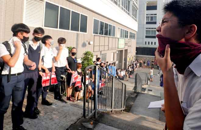 Pelajar sekolah menengah melaungkan slogan ketika membentuk rangkaian manusia bagi mengecam keganasan polis terhadap penunjuk perasaan, selepas pertempuran meletus di daerah Wan Chai, semalam. — Gambar Reuters