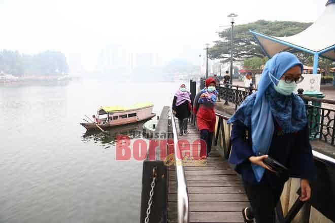Orang ramai dilihat menggunakan penutup hidung dan mulut di Tebingan Kuching.