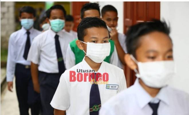 Murid Sekolah Kebangsaan (SK) Gita yang menduduki peperiksaan UPSR dilihat menggunakan topeng hidung dan mulut di Kuching hari ini. - Gambar oleh Muhammad Rais Sanusi
