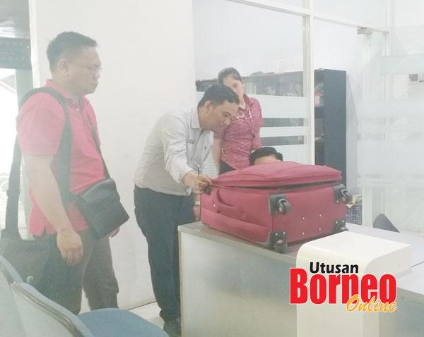 Saibi (kiri) memerhati kakitangan syarikat penerbangan memeriksa begnya yang terkopek ketika membuat aduan.