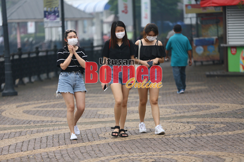 Orang ramai menggunakan penutup hidungan dan mulut ekoran jerebu teruk yang melanda Kuching. - Gambar oleh Muhammad Rais Sanusi