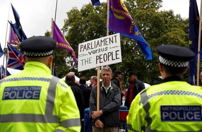 Dua polis berkawal ketika penunjuk perasaan pro-Brexit berhimpun di luar bangunan parlimen di Westminster di London, Britain kelmarin. — Gambar Reuters
