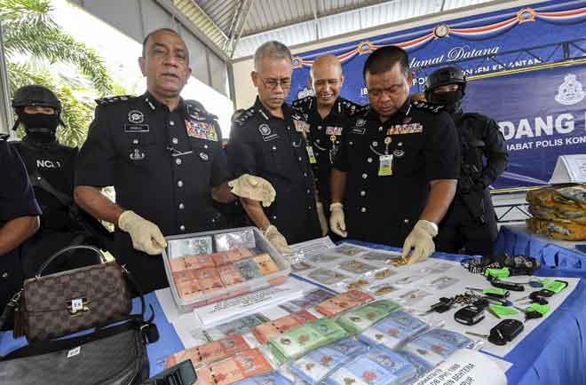 Mohd Khalil  (dua kiri) bersama Hasanuddin (empat kanan) menunjukkan sejumlah wang tunai yang dirampas dalam Op Toucan dan Op Damn Tokan pada sidang media di Ibu Pejabat Polis Kontinjen Kelantan semalam. — Gambar Bernama