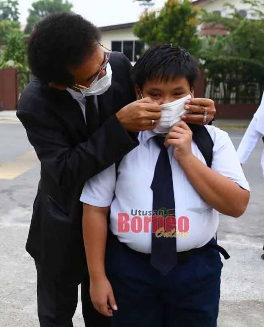 Salah seorang guru SK Gita, Kuching membantu calon UPSR memakai penutup mulut dan hidung sebelum memasuki dewan peperiksaan, semalam. — Gambar Muhammad Rais Sanusi