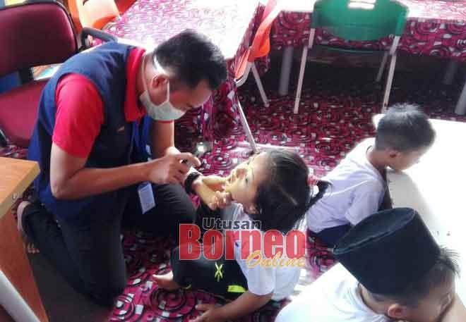 Gambar fail menunjukkan petugas perubatan memeriksa kanak-kanak bagi mengesan tanda-tanda HFMD.