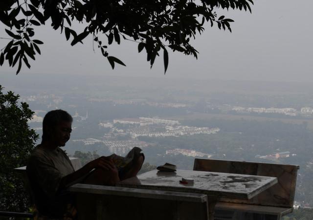 Seorang pengunjung Anjung Indah, Balik Pulau kelihatan membaca akhbar harian berlatar belakangkan pemandangan yang kabur berikutan keadaan jerebu yang melanda di negeri ini.