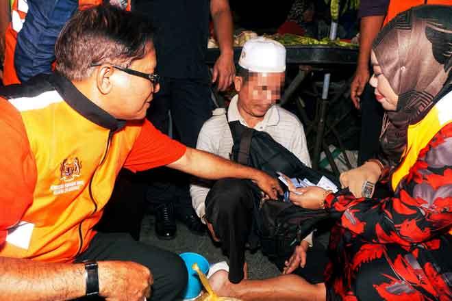 Halimaton (kanan) memeriksa beg seorang pengemis warga Kemboja pada Program Kesedaran Pencegahan Pengemisan dan Operasi Menyelamat Orang Papa di Pasar Malam Kepala Batas semalam. — Gambar Bernama