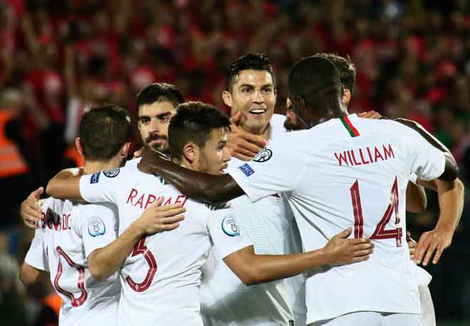 Ronaldo (tengah) dikerumuni oleh rakan sepasukan selepas menjaringkan gol kedua Protugal pada aksi di Vilnius, Lithuania Selasa lepas. — Gambar AFP