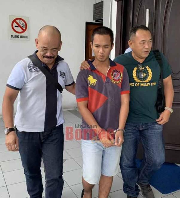 Raymond (tengah) dibawa keluar dari Mahkamah Sesyen Sibu, semalam.