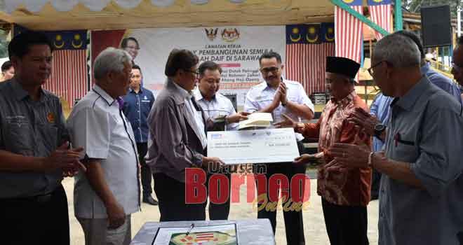 Abang Johari menyampaikan replika cek bernilai RM10, 000 untuk PIBG SK Sungai Tisang kepada wakil penerima pada majlis berkenaan.