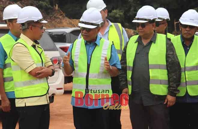 Masing (dua kanan) mendengar taklimat daripada Cassidy (kiri) semasa melakukan tinjauan pembinaan jalan berkenaan.